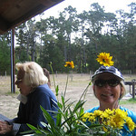 Karen Letendre, framed by calendulas puts on a smile, while Marilyn Green orders a soft drink.
